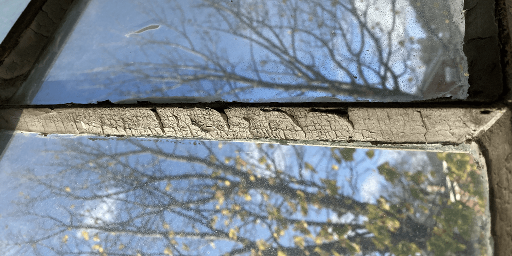 Asbestos paint chipping of the window of an older home.